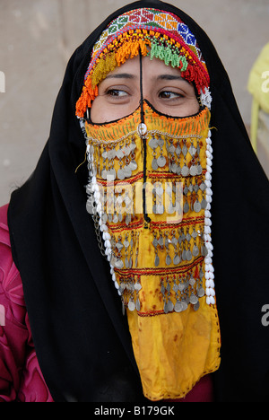 A Bedouin woman in Sinai is wearing an old traditional colorful face cover, called burqa - Stock Photo