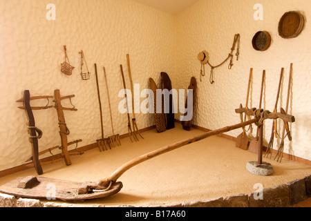 Threshing equipment and animla yokes in the Museu do Cardina museum on the Portuguese Atlantic island of Porto Santo. - Stock Photo