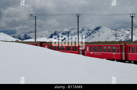 Bright red train carriages appearing from snow covered mountain slopes in the Swiss alps. Full of tourists on a - Stock Photo