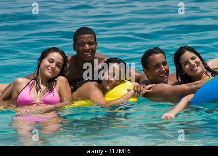 Multi-ethnic friends on floats in water - Stock Photo