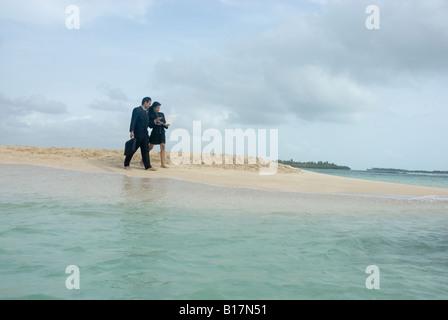 Hispanic businesspeople walking on beach - Stock Photo