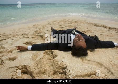 Hispanic businessman laying on beach - Stock Photo