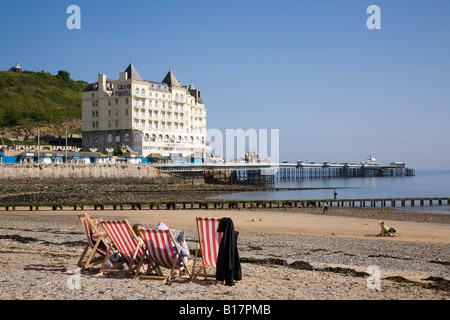 Llandudno North Wales UK Seaside resort with red and white striped deckchairs on quiet North Beach with hotel on - Stock Photo