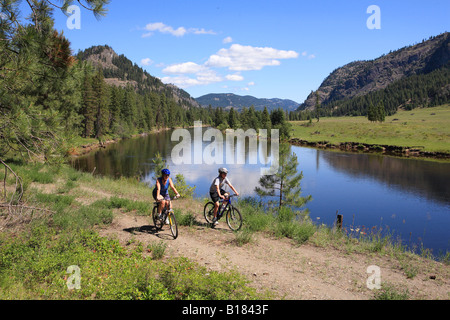 Two mountain bikers along Kettle River on the Trans Canada Trail Kettle Valley RR rail bed, Kettle River Provincial - Stock Photo