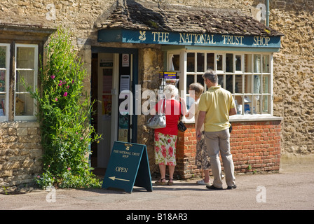 Tourists visiting a shop in the lovely English village of Lacock viewed from public highway - Stock Photo
