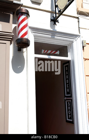barber shop with traditional striped pole outside in enniskillen county fermanagh - Stock Photo
