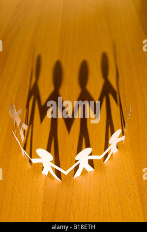 Paper Man Chain With Long Shadow On Wooden Table Symbol Of Unity