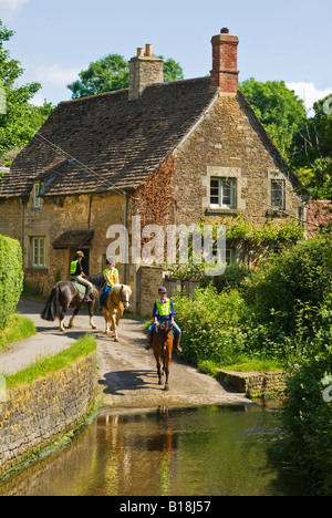 Young horse riders in the quiet historic English village of Lacock - Stock Photo