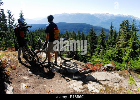 Two Mountain Bikers on the descent from Khyber Pass, Whistler, British Columbia, Canada. - Stock Photo