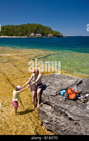 Young woman with daughter on Niagara Escarpment near Boulder Beach along Bruce Trail, Bruce Penninsula National - Stock Photo