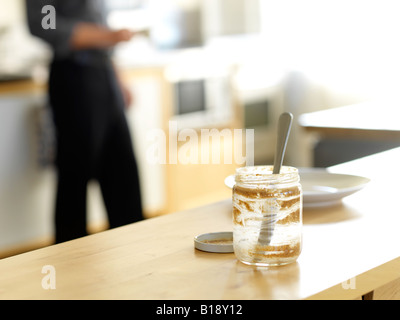 business man in loft kitchen with an empty nut spread jar in the foreground, Montreal, Quebec, Canada. - Stock Photo