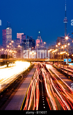 Rush-hour traffic on QEW (Queen Elizabeth Way) and Toronto city skyline, Toronto, Ontario, Canada. - Stock Photo