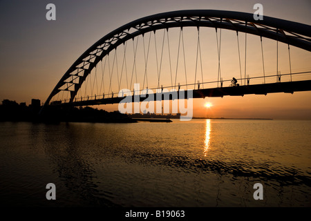 Cyclist crosses Humber River Pedestrian Bridge at sunrise with Toronto skyline in background, Toronto, Ontario, - Stock Photo