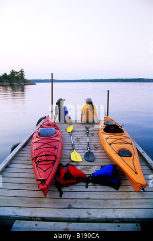 Kayakers relaxing on Nutimik Lake campground boat dock, Whiteshell Provincial Park, Manitoba, Canada. - Stock Photo