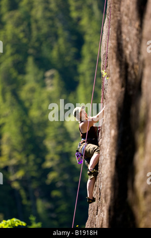 Female rock climber on Red Earth (5.9) Main Wall Crest Craigs in Strathcona Park.  Vancouver Island, British Columbia, - Stock Photo