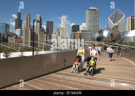 PARKS Chicago Illinois BP Bridge Frank Gehry design in Millennium Park skyline stainless steel curves many people - Stock Photo