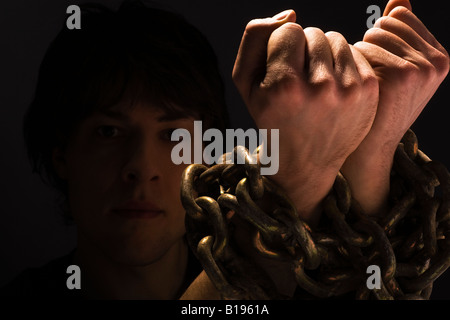 Man with chains on his wrists - Stock Photo