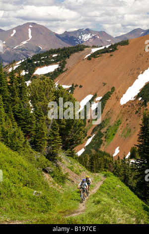 Two men ascend towards the summit of Windy Pass in the Southern Chilcotin Mountains.  British Columbia, Canada. - Stock Photo
