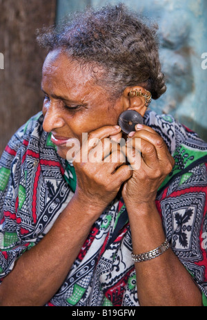 Kenya, Lamu archipelago, Pate Island. An old woman on Pate Island inserts a buffalo horn earplug into her pierced - Stock Photo