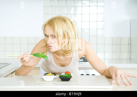Woman leaning over food, looking at camera threateningly - Stock Photo