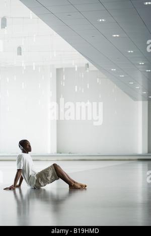 Teen boy sitting on floor, listening to headphones - Stock Photo