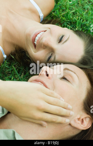 Mother and teen daughter lying on the ground, girl touching woman's face, cropped view - Stock Photo
