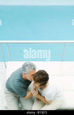 Couple sitting on balcony, man kissing woman's cheek, high angle view - Stock Photo