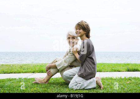 Grandmother and grandson sitting outdoors together, smiling, sea in background - Stock Photo