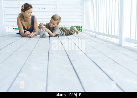 Mother and son lying on porch, looking at jar together - Stock Photo
