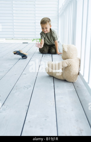 Little boy on porch, playing with toy car, smiling - Stock Photo