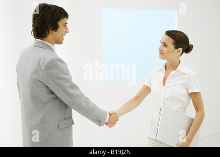 Two young professionals shaking hands, smiling - Stock Photo