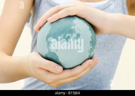 Child holding globe in hands, close-up - Stock Photo