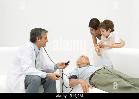 Doctor measuring elderly man's blood pressure, family watching - Stock Photo