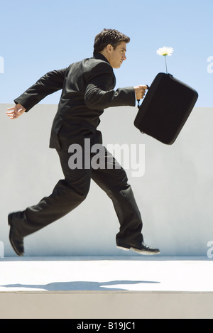 Businessman running in midair, holding briefcase with flower sticking out, side view - Stock Photo
