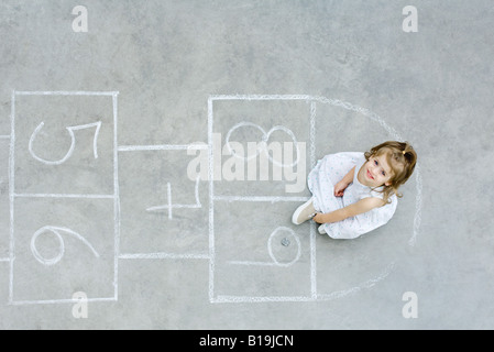 Girl sitting down on hopscotch grid, looking up, overhead view - Stock Photo