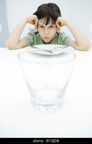 Boy sulking at kitchen table, leaning on elbows, empty glass in foreground - Stock Photo
