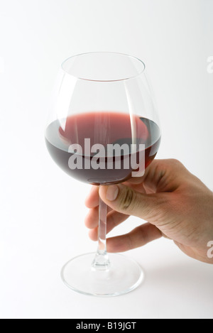 Hand holding glass of red wine, close-up - Stock Photo