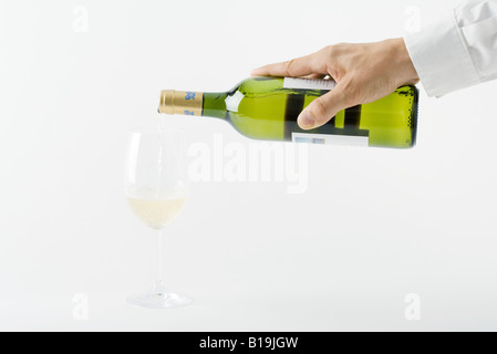 Man's hand pouring white wine into glass, cropped view - Stock Photo