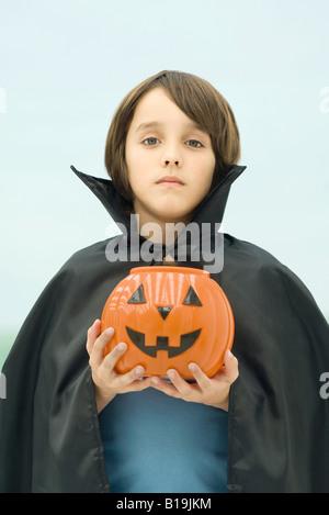 Boy dressed in vampire costume, holding jack o' lantern, portrait - Stock Photo