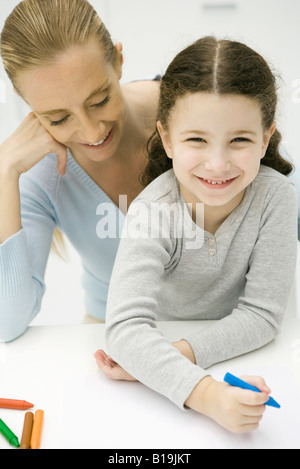Little girl sitting on mother's lap, coloring, smiling at camera - Stock Photo