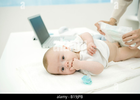 Mother changing baby's diaper on desk, laptop in background - Stock Photo