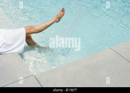 Woman sitting beside swimming pool, splashing water with feet, cropped view - Stock Photo