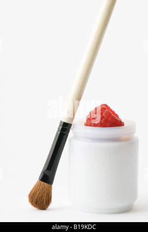 Make-up brush and raspberry in small container - Stock Photo