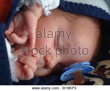Sleeping Newborn baby babies asleep eyes closed hands fingers finger hand touching dreaming dream face human - Stock Photo