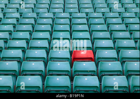 One red seat amongst rows of green seats in a sports stadium - Stock Photo