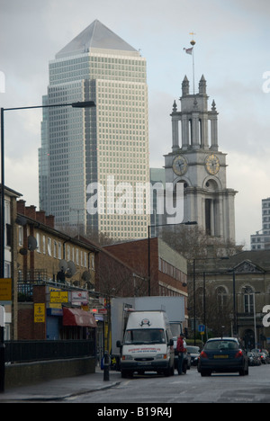 Street view in Limehouse London towards two contrasting buildings, St Anne's Limehouse church and Canary Wharf tower - Stock Photo