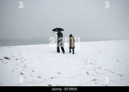 People walking on a snow covered beach in Hove, East Sussex, UK - Stock Photo