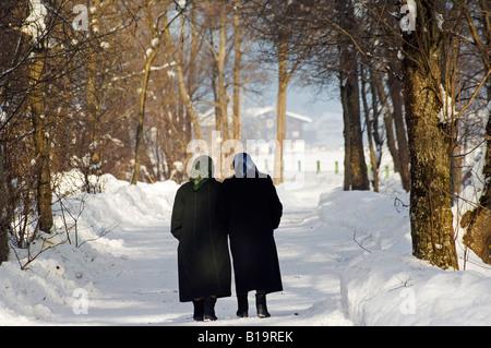 Mayrhofen Ski Resort, Hippach Village, Old women walking in snow - Stock Photo