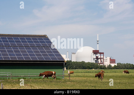 The atomic power plant in Brokdorf in the front solar plants on the roof of a cowshed - Stock Photo