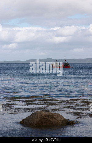Fishing boat leaving sannox on the isle of arran, travelling out across the firth of clyde, with a foreground rock - Stock Photo